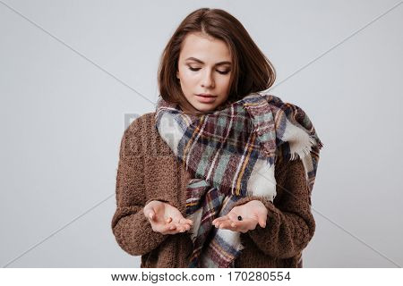 Picture of sick young woman in sweater and scarf choosing medicine pills. Isolated over gray background.