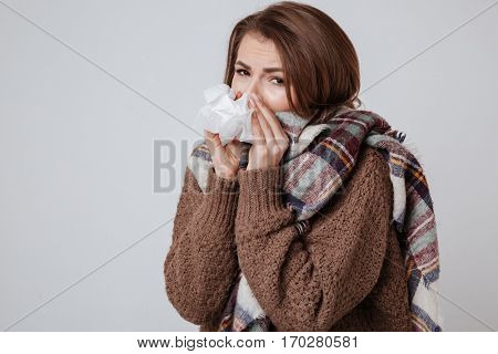 Image of sick young woman in sweater and scarf standing with napkin isolated over gray background.