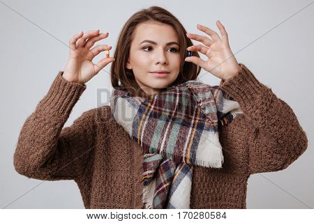 Image of sick young lady in sweater and scarf choosing medicine pills. Isolated over gray background.