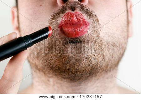 Bearded Man Transvestite or Gay Makes Up Lips with Lipstick.