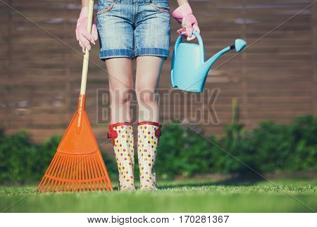 Woman wearing gloves and wellington boots holding rake and water can, spring gardening concept