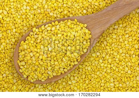 Closeup of dried Hulled and split mung bean in yellow without green skin on wooden spoon