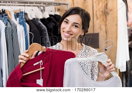Young woman trying on new dresses in clothing store. Confused young woman choosing between two shirts to buy one. Smiling girl looking at camera and holding two dresses to compare the better one.