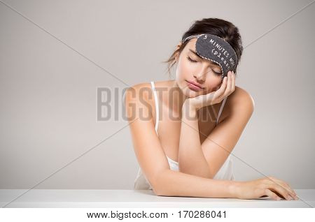 Sleepy woman on table with copy space. Beauty young woman in pajamas smiling and sleeping with eye mask on head. Tired woman resting and dreaming with sleeping mask isolated on grey background.