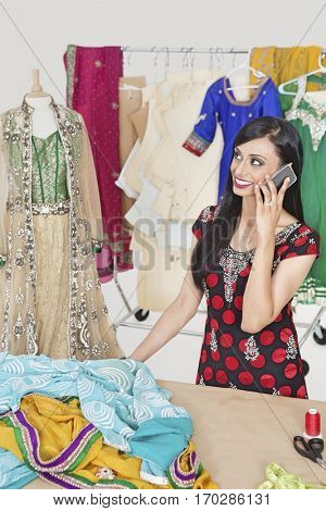 Beautiful Indian female dressmaker answering phone call while standing at table