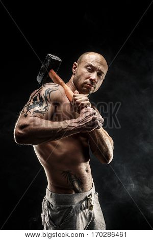 Portrait of serious muscular topless man with sledgehammer looking at camera