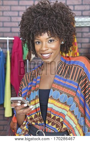 Portrait of an African American female fashion designer using cell phone