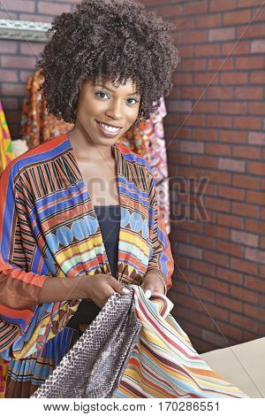 Portrait of an African American female dressmaker holding fabric