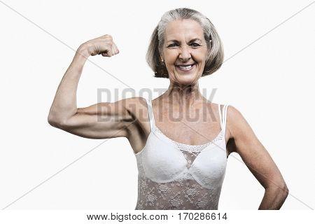 Portrait of senior woman flexing muscles against white background