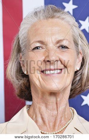 Portrait of smiling senior woman against American flag
