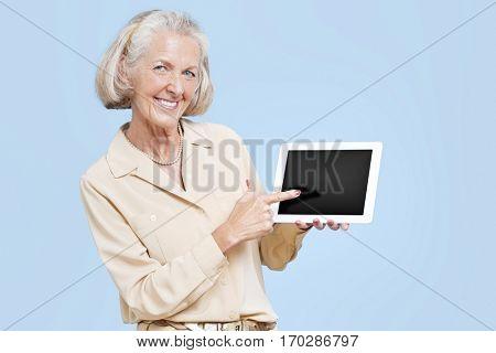 Portrait of senior woman showing tablet PC against blue background