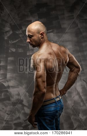 Shirtless muscled fitness man. Cool looking. Tough guy. Brown eyes. Bald. Tanned skin. Studio shot on grey abstract background. Back side wiew.