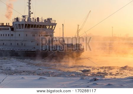 Arkhangelsk, Russia - february 8, 2017: Diesel Electric Ice Breaker Kapitan Evdokimov Breaks Ice at Sunset. Nothern Dvina River.