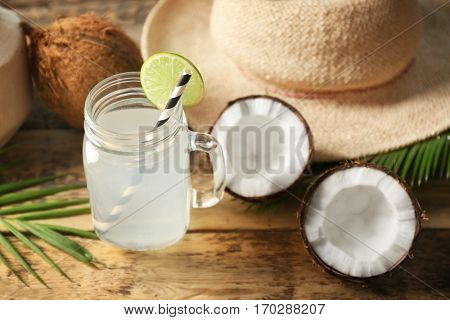 Mason jar with coconut water and fresh nut on wooden table