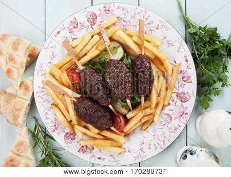 Turkish kofta kebab, minced meat skewer with french fries and flatbread