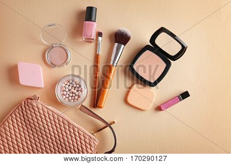 Cosmetic bag and makeup products on color   background
