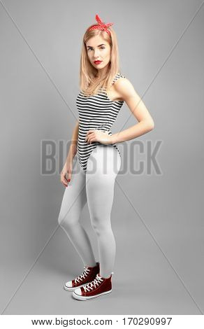 Woman in white tights and sneakers on gray background