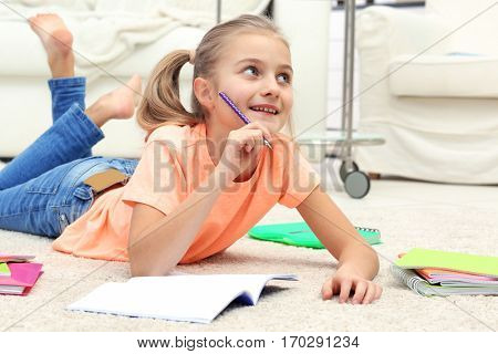 Attractive little girl lying on the floor and writing in copybook