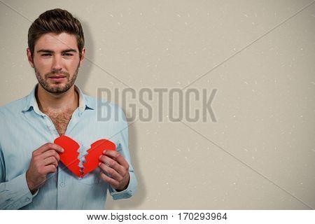 Sad man holding heart halves against grey