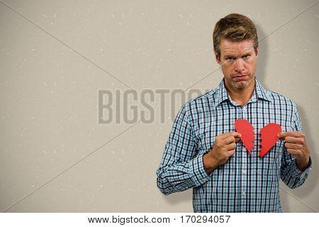 Sad man with broken heart against cream