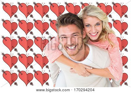 Handsome man giving piggy back to his girlfriend against perforated heart symbols