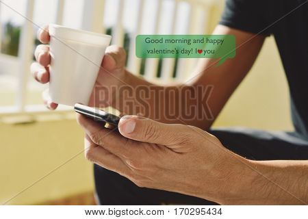 closeup of a young caucasian man with a cup of coffee in his hand sending or reading a text message with a smartphone with the text good morning and happy valentines day, I love you