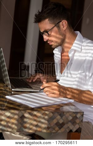 Handsome men working on lap top, writing resume