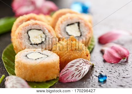 Tempura Maki Sushi - Deep Fried Sushi Roll made of Cream Cheese inside. Salmon outside. Japanese Sushi Food and Natural Flower Concept