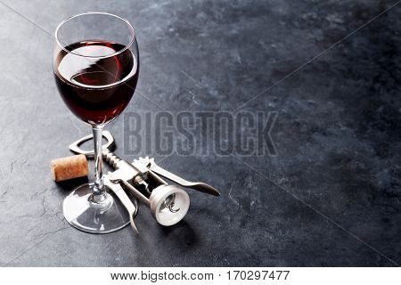 Red wine glass and corkscrew on stone background. With copy space