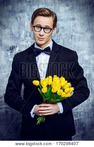 Posh young man in an elegant suit with a bouquet of yellow tulips. Valentine's Day, Women's Day, Mother's Day. Wedding concept.