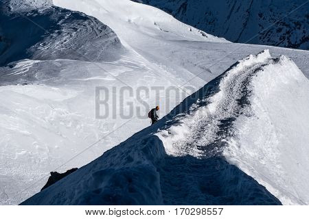 Chamonix France - December 30 2016: Climber ascending final stretch on arete ridge leading up to Aiguille du Midi in early winter sunny conditions