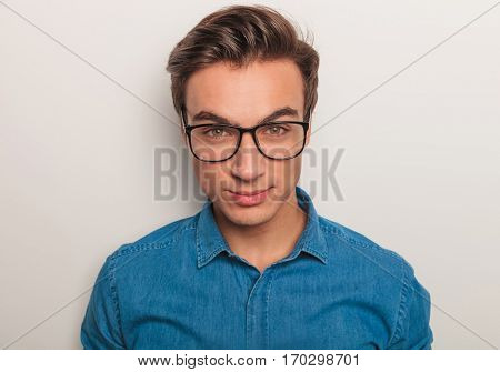 closeup picture of a young man wearing glasses , studio picture