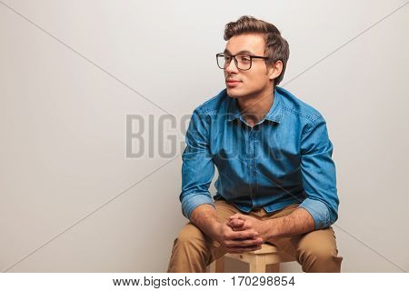 seated young student is thinking , side view on grey background
