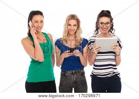 happy women communicating in different ways; one talking on the phone, one texting and one sending an email on her tablet pad; isolated on white background