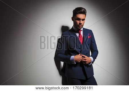 confident businessman buttoning his suit and looks at the camera, leaning on a grey studio wall