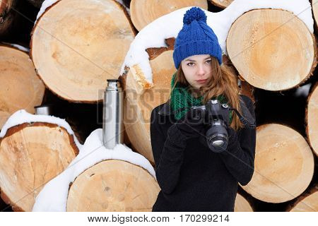 Young Very Positive Woman In Sweater Blue Funny Knitted Hat Posing With Dslr Camera In Winter Forest