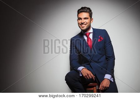 side view of a smiling gentleman sitting on a chair in studio and looks to side
