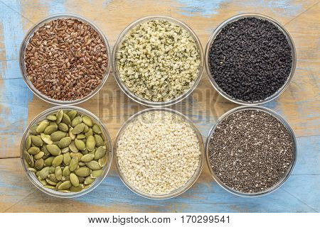 healthy seed collection (chia, hemp hearts, brown flax, pumpkin, black cumin, sesame) - top view of small glass bowls against grunge wood