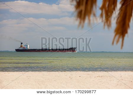 Oil tanker sailing past empty tropical beach with palm tree and white sand