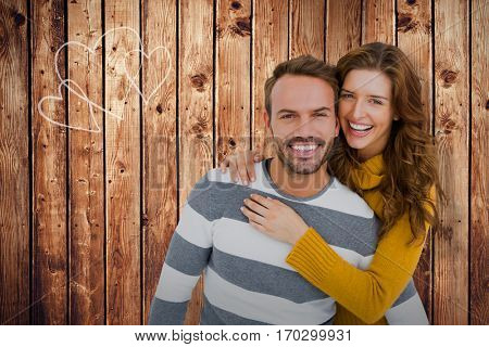 Portrait of cheerful young couple embracing against wooden planks