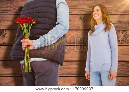 Man hiding roses behind back from woman against blue paint splashed surface