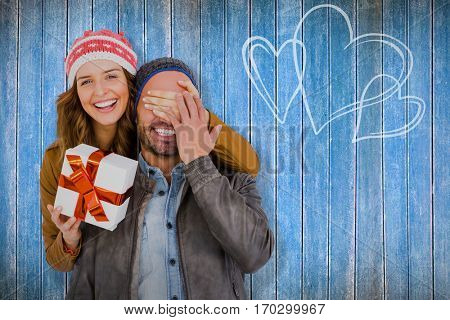 Portrait of woman giving surprise gift to man against wooden planks