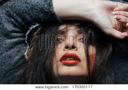 Emotional portrait of attractive young woman against dark background