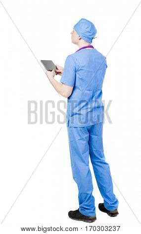 Back view of doctor in robe holding tablet computer. Standing young guy. Rear view people collection.  backside view of person.  Isolated over white background.