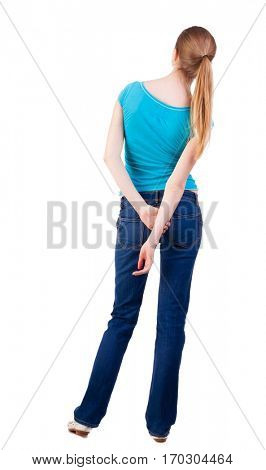 back view of standing young beautiful  blonde woman in blue t-shirt and jeans. she shyly looks at something. girl  watching. Rear view people collection.