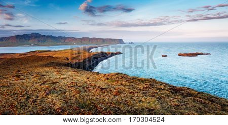 Great view on Kirkjufjara beach and sunny hills. Popular tourist attraction. Picturesque and gorgeous scene. Location place Sudurland, cape Dyrholaey, Vic village, South Iceland, Europe. Beauty world.