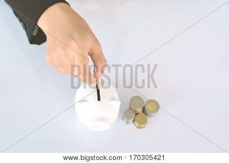 Businesswomen holding coin and white piggy bank on blue background selective and soft focus