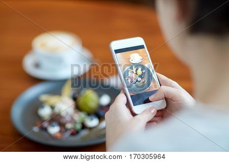 food, new nordic cuisine, technology, eating and people concept - woman with smartphone photographing chocolate ice cream dessert with blueberry kissel, honey baked fig and greek yoghurt at cafe