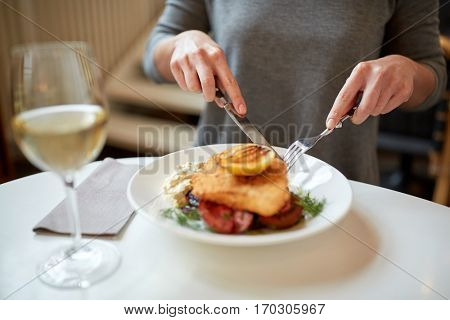 food, new nordic cuisine and people concept - woman eating breaded fish fillet with tartar sauce and oven-baked beetroot tomato salad with fork and knife at cafe or restaurant
