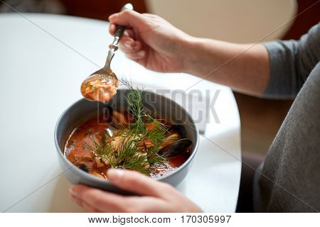 food, new nordic cuisine and people concept - woman eating seafood soup with fish and blue mussels at cafe or restaurant